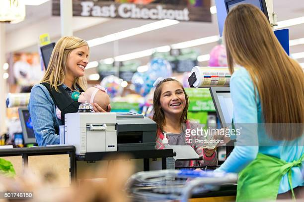 Cashier giving change to young customer in grocery store
