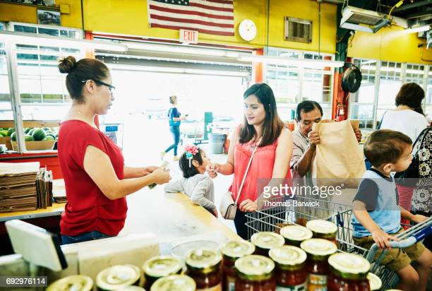 Cashier giving woman change as she checks out from produce market