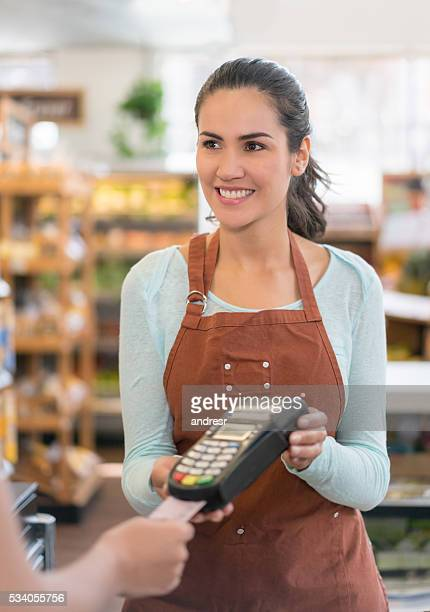 Cashier holding a credit card machine at a supermarket