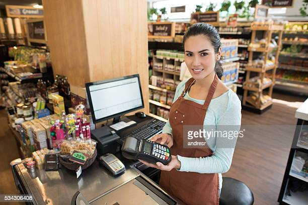 Cashier holding a credit card machine at the supermarket