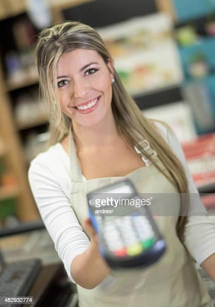 Cashier holding a credit card reader machine