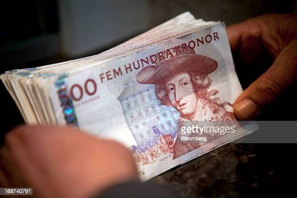 A cashier holds Swedish 500 kronor notes in this arranged photograph inside a currency exchange in Malmo Sweden on Tuesday May 14 2013 Sweden's krona...