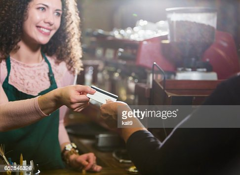 Cashier in coffee shop takes payment card from customer : Stock Photo
