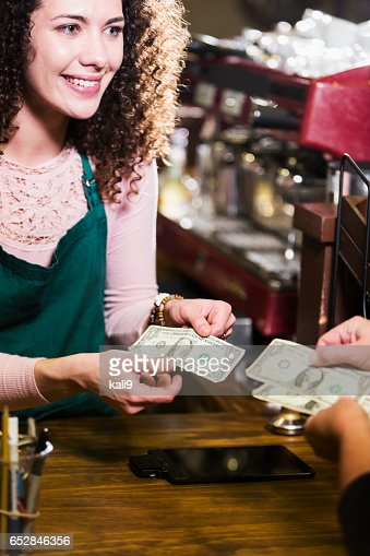 Cashier in coffee shop taking cash from customer : Stock-Foto