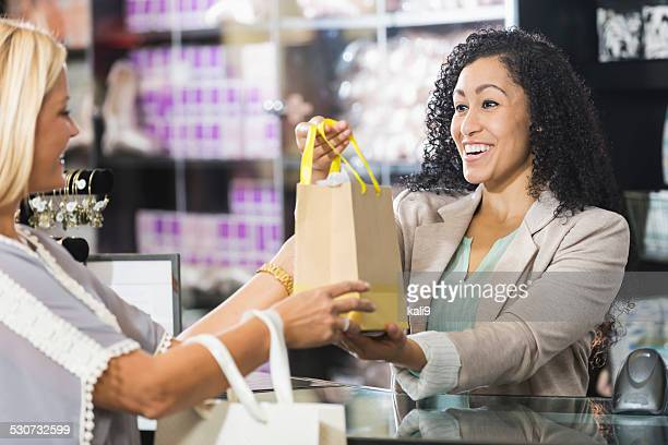 Cashier in retail store handing customer shopping bag