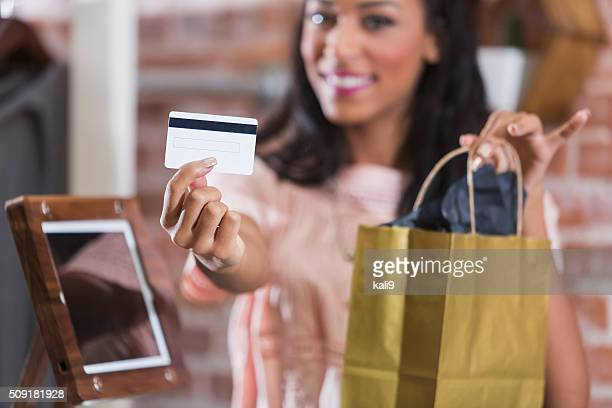 Cashier in store holding credit card and shopping bag