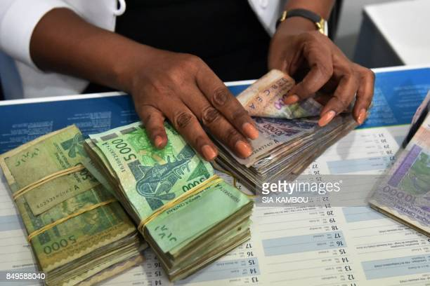 A cashier of the Ecobank Ivory Coast counts notes on September 18 2017 in Abidjan EcobankIvory Coast the Ivorian subsidiary of panAfrican bank...