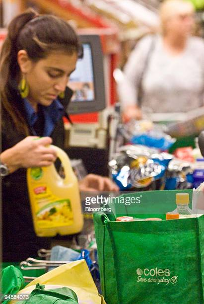 A cashier packs up a shopping bag at the checkout counter of a Coles Group Ltd supermarket in Sydney Australia on Saturday July 7 2007 Wesfarmers Ltd...
