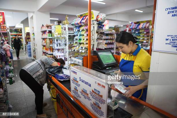 A cashier processes a customer's goods at the checkout desk of a Nomin Holding supermarket in Ulaanbaatar Mongolia on Saturday Aug 12 2017 The...