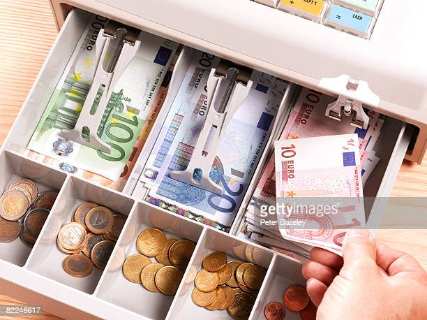 Cashier putting Euro notes in cash register
