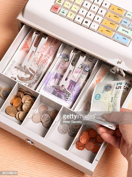 Cashier putting pounds sterling in cash register