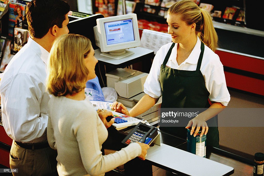 Cashier serving man and woman at checkout counter in store : Stock Photo