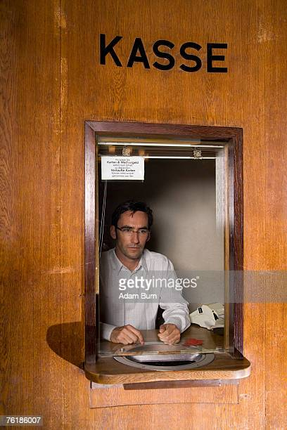 A cashier sitting in a box office