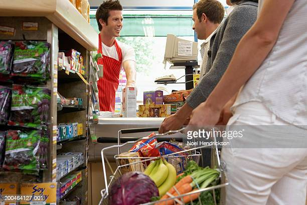 Cashier smiling at customer on checkout line in supermarket, close-up