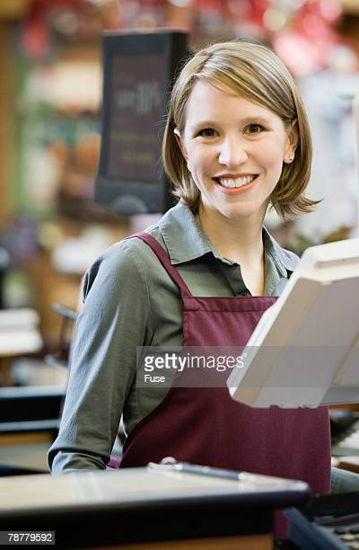 Cashier Standing at Supermarket Checkout