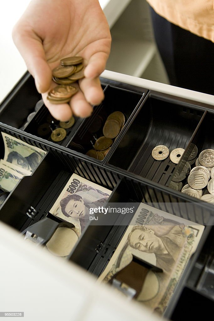 Cashier taking out coins from cash register : Stock Photo