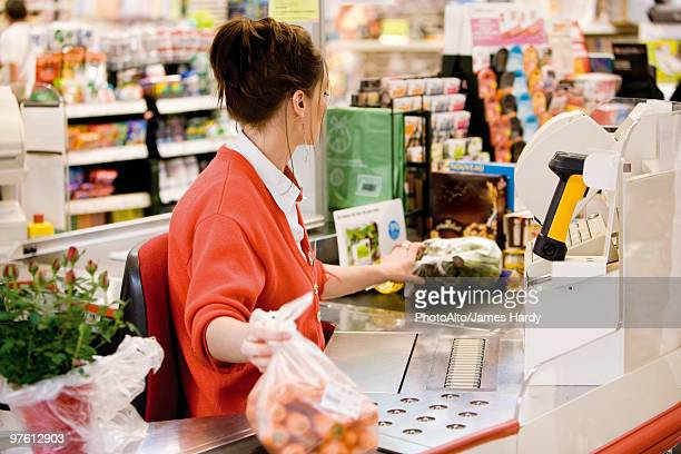 Cashier totaling grocery purchases