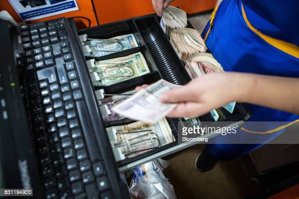 A cashier works the cash register at the checkout desk of a Nomin Holding supermarket in Ulaanbaatar Mongolia on Saturday Aug 12 2017 The Mongolian...