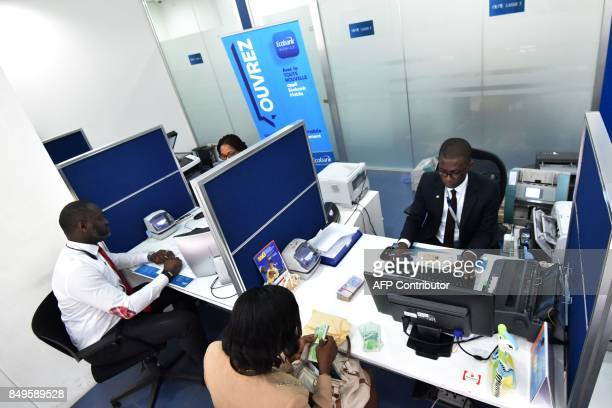 Cashiers and clients of a Ecobank Ivory Coast bank are pictured on September 18 2017 in Abidjan EcobankIvory Coast the Ivorian subsidiary of...