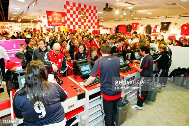 Cashiers serve fans in the club shop before the Barclays Premiership match between Liverpool and Sheffield United at Anfield on February 24 2007 in...