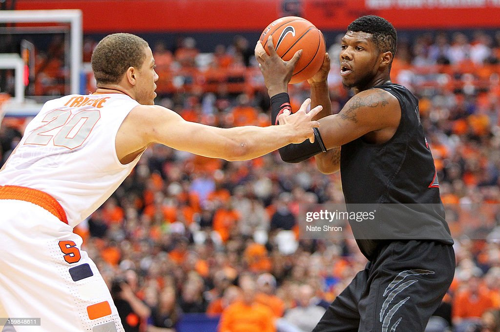 Cashmere Wright #2 of the Cincinnati Bearcats attemtps to pass the ball against Brandon Triche #20 of the Syracuse Orange during the game at the Carrier Dome on January 21, 2013 in Syracuse, New York.