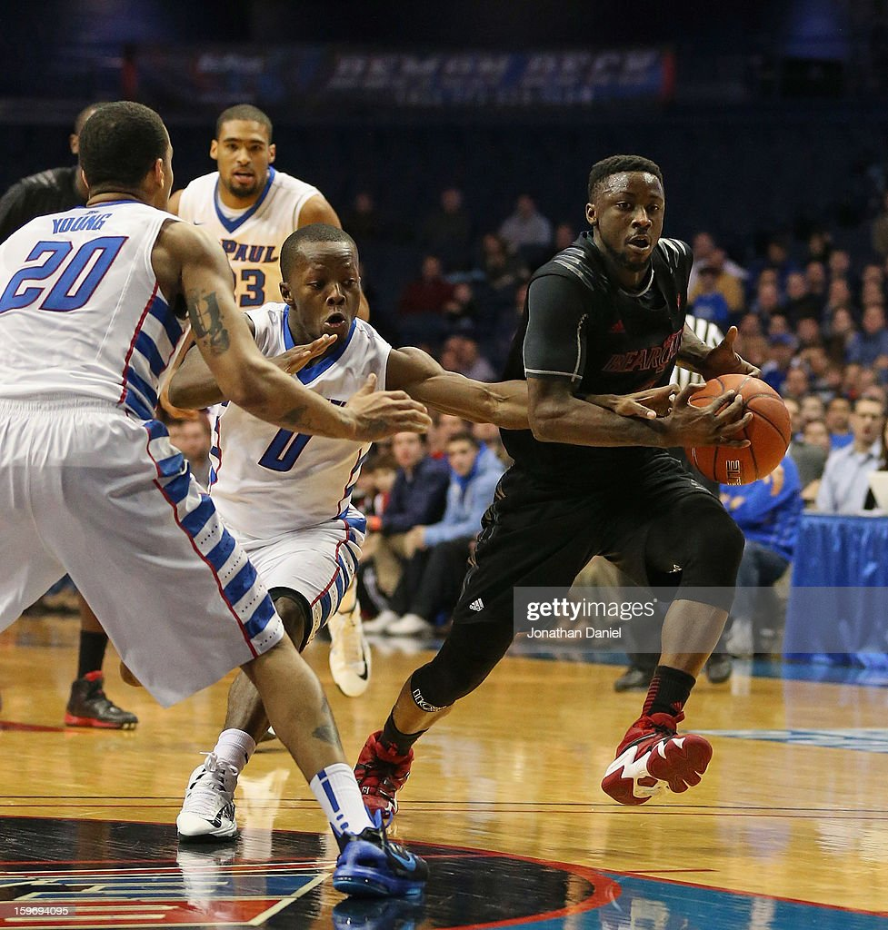 Cashmere Wright #1 of the Cincinnati Bearcats moves past Worrell Clahar #0 and Brandon Young #20 of the DePaul Blue Demons at Allstate Arena on January 15, 2013 in Rosemont, Illinois. Cincinnati defeated DePaul 75-70.