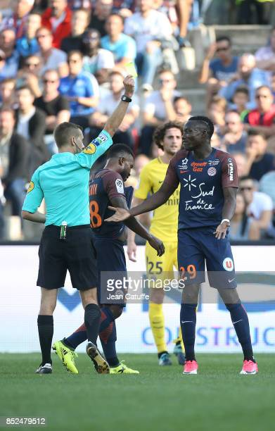 Casimir Ninga of Montpellier receives a yellow card from referee Clement Turpin during the French Ligue 1 match between Montpellier Herault SC and...