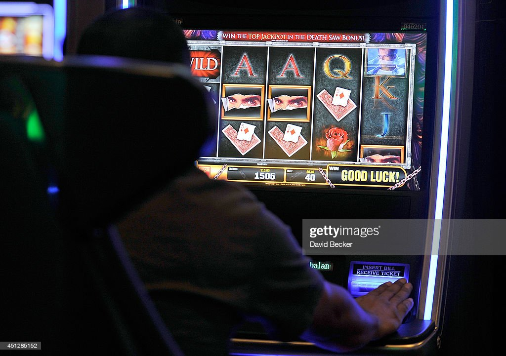 Casino patron Manuel Guzman of California plays the slot machine, 'The Magic of David Copperfield,' by Bally Technologies at the MGM Grand Hotel/Casino on June 26, 2014 in Las Vegas, Nevada.