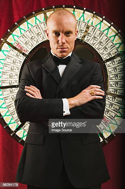 Casino worker in front of the wheel of fortune