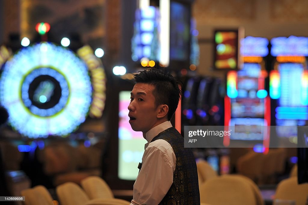 A casino worker looks on at the Sands Cotai Central casino before the opening of the resort in Macau on April 11, 2012. Las Vegas Sands Corp. opened its fourth casino in the booming Asian gaming capital of Macau transforming a 'swamp' earmarked for a fireworks factory into a $5 billion resort. AFP PHOTO / AARON TAM
