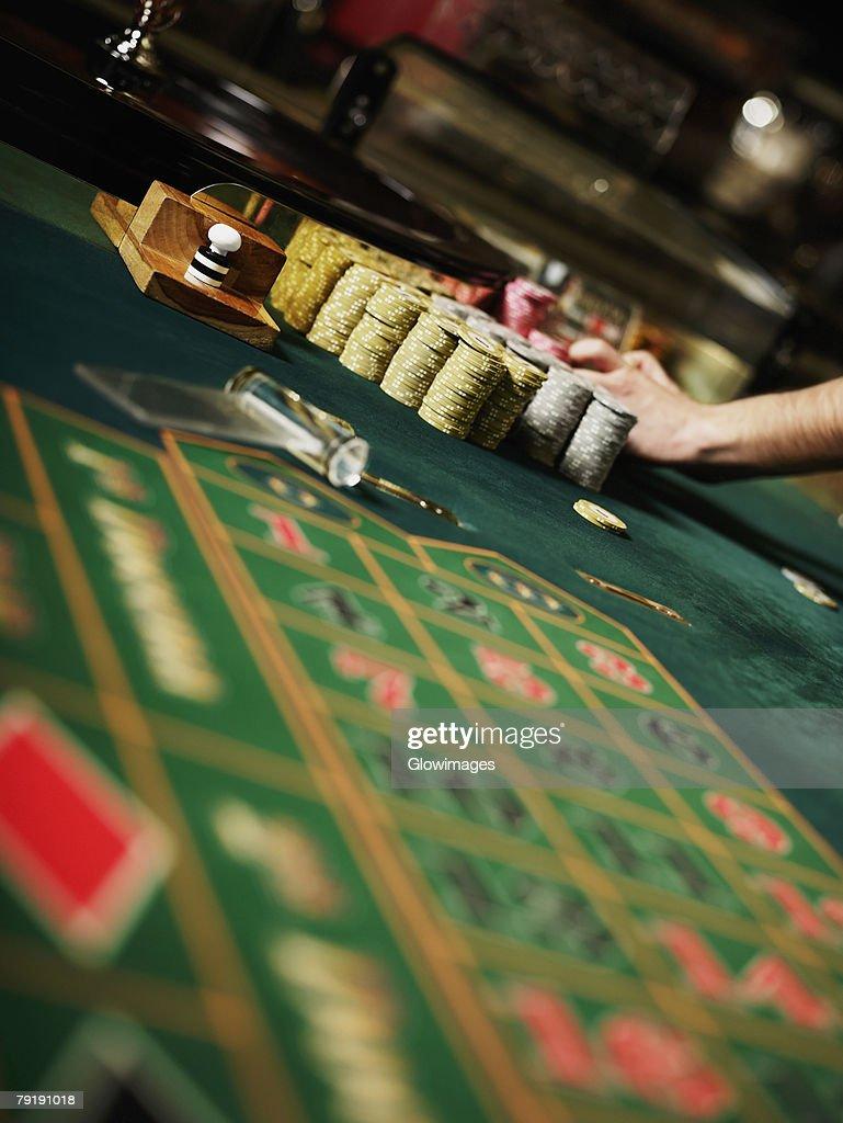 Casino worker's hand arranging gambling chips on a gambling table : Foto de stock