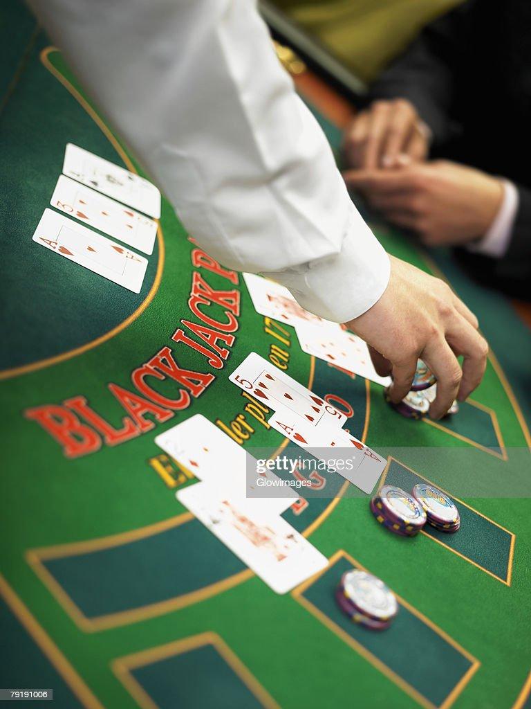 Casino worker's hand placing gambling chips on a gambling table : Foto de stock