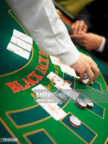 Casino worker's hand placing gambling chips on a gambling table : Foto de stock