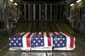 BASE GUAM Caskets bearing the remains of US soldiers found in Laos sit aboard a USAF C17A Globemaster III aircraft at Anderson Air Force Base in Guam...