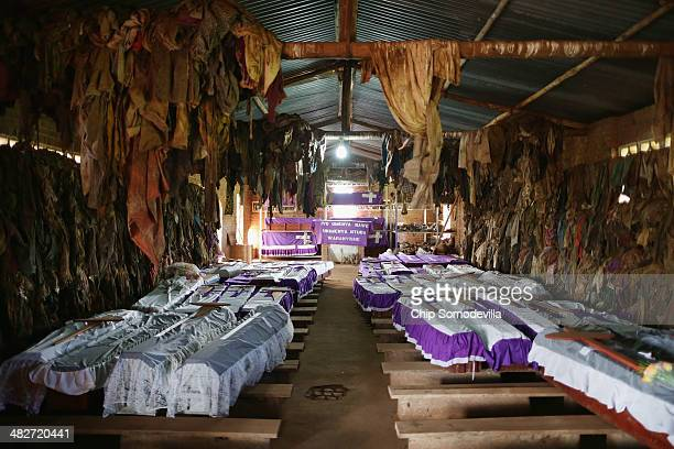 Caskets holding the remains of many victims rest on pews as their bloodstained clothing hangs from the rafters inside the Ntarama Catholic Church...