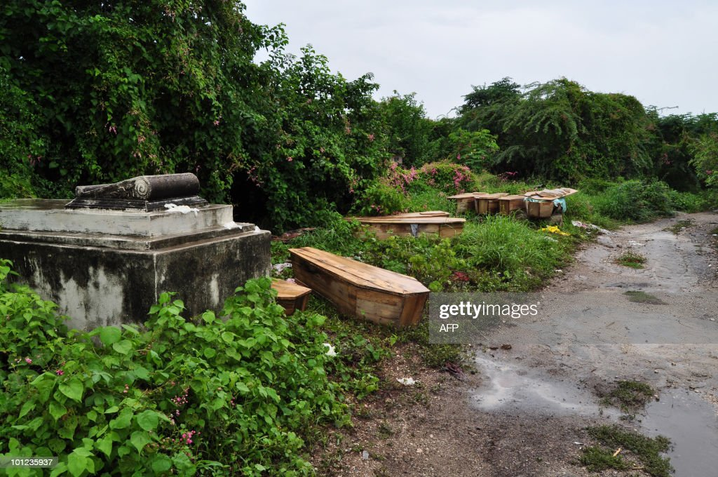 Caskets of victims of the violence in Kingston are left in the May Pen Cemetery of the Jamaican capital on May 28, 2010. Jamaican police and soldiers have killed 73 people since Sunday in an effort to capture Christopher 'Dudus' Coke, a powerful leader in the Kingston slums who is sought by the United States on drug trafficking charges. AFP PHOTO/Ratiba HAMZAOUI
