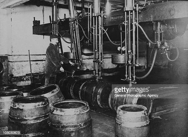 Casks are filled with beer at a brewery in Germany circa 1920