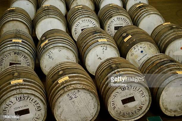 Casks containing whisky sit in a warehouse at Suntory Holdings Ltd's Yamazaki distillery in Shimamoto Osaka Japan on Friday Sept 13 2013 Suntory is a...