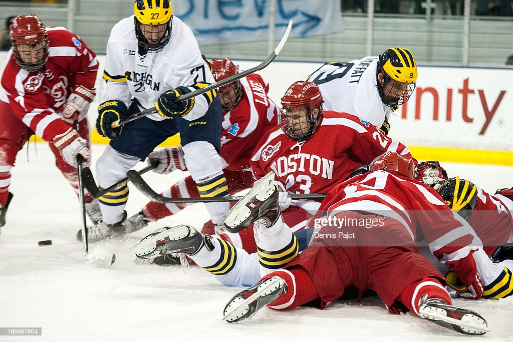 Cason Hohmann #7 of the Boston University Terriers battles against Alex Guptill #27 of the Michigan Wolverines on October 25, 2013 at Yost Ice Arena in Ann Arbor, Michigan.