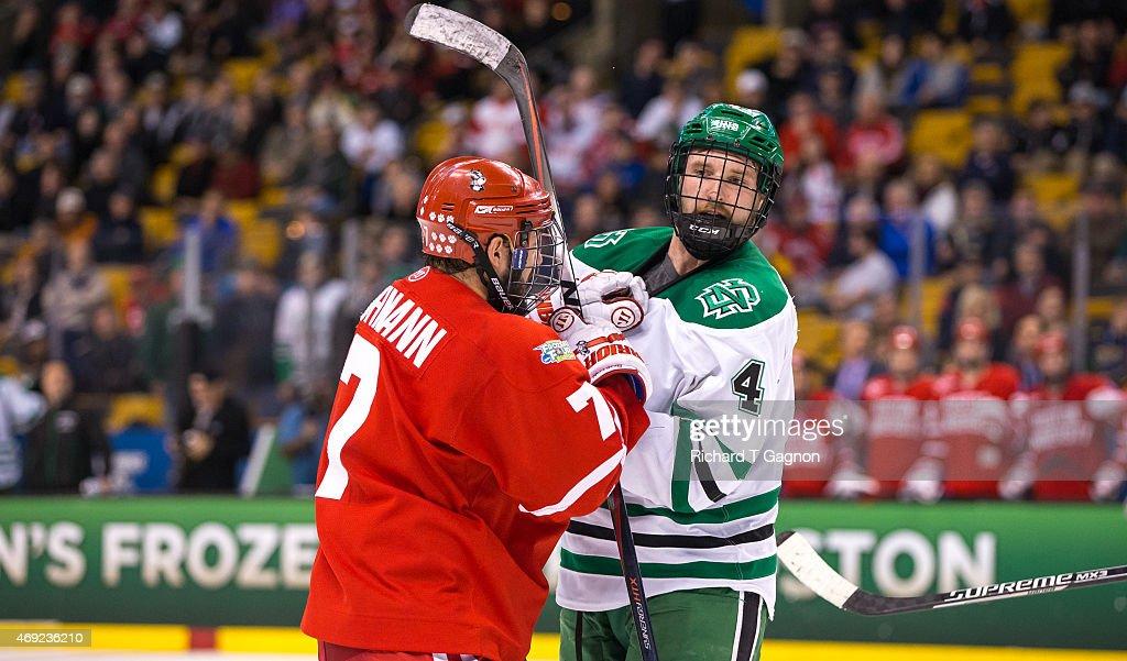 Cason Hohmann of the Boston University Terriers tangles with Keaton Thompson of North Dakota during the 2015 NCAA Division I Men's Hockey Frozen Four...