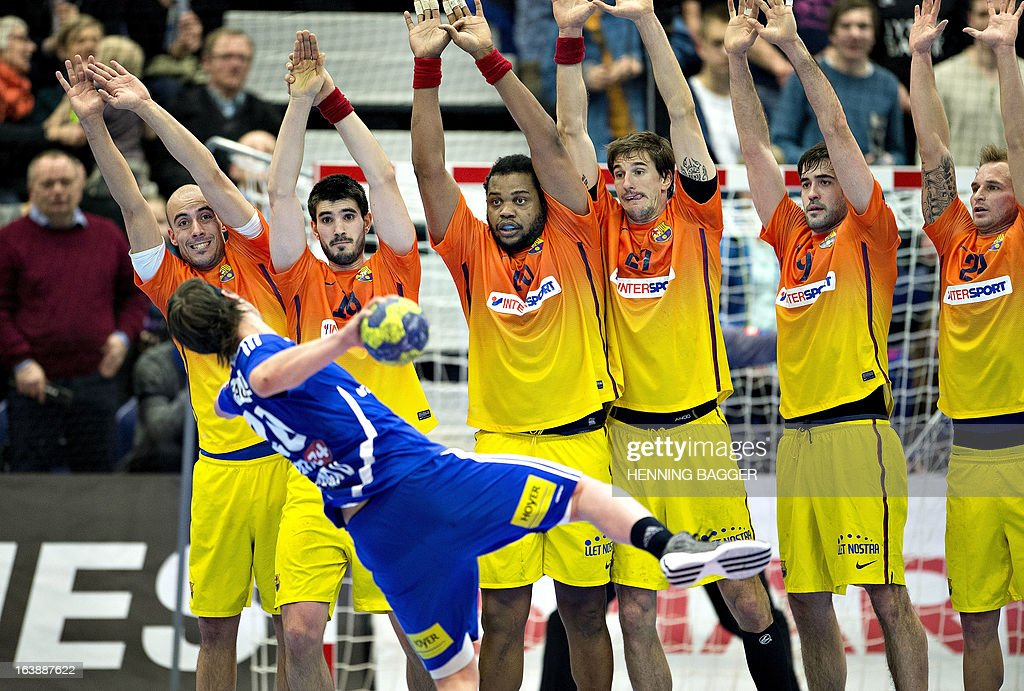 Casper Mortensen (L, blue jersey) of BSV Bjerringbro-Silkeborg tries to score despite a massive defence from players of FC Barcelona Intersport during their men's handball Champions League round of sixteen first leg match in Herning, Denmark, on March 17, 2013.