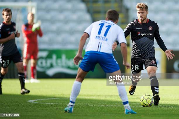 Casper Nielsen of OB Odense and Yann Rolim of AaB Aalborg compete for the ball during the Danish Alka Superliga match between OB Odense and AaB...
