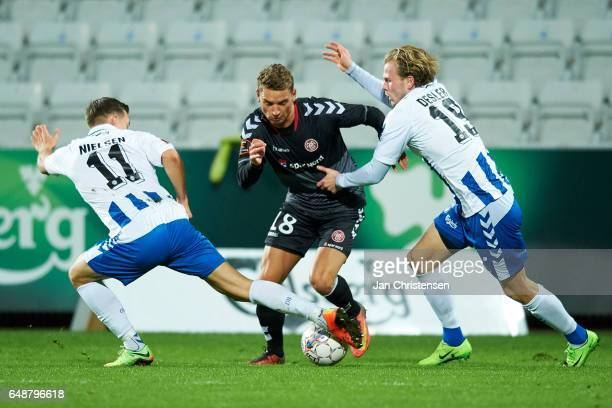 Casper Nielsen of OB Odense Rasmus Thellufsen of AaB Aalborgand Mikkel Desler of OB Odense in action during the Danish Alka Superliga match between...