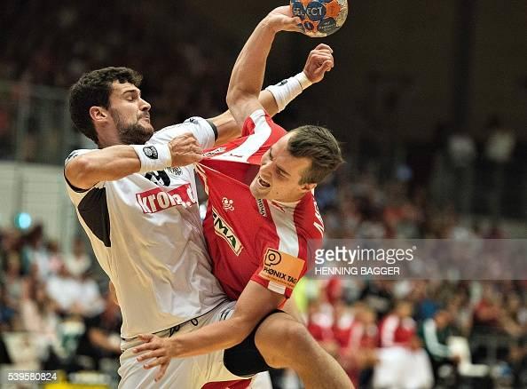 Casper U Mortensen of Denmark is tackled by Dominik Bammer of Austria during their men's World Championship handball qualification match between...