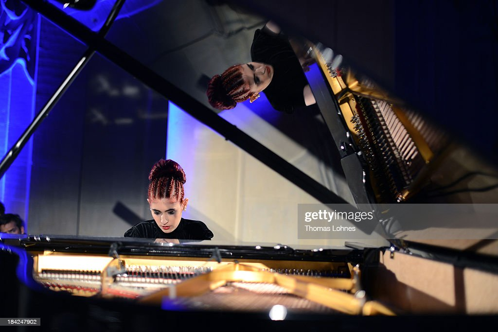 Cassandra Wyss performes at the piano during the Minx fashion night at Residenz on October 12, 2013 in Wuerzburg, Germany. The benefit of the charity gala is for the aid organisation 'Sauti Kuu' of Auma Obama. Behind the fashion label Minx stands Eva Lutz.