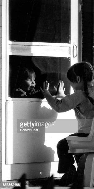 Cassidy Quintana age 4 on the front porch her sister Elizabeth Quintana 16 mts inside the screen door 34th and Raleigh in northwest Denver Credit The...