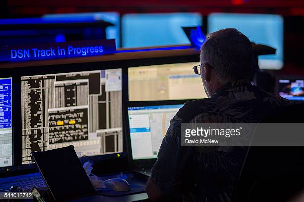 Cassini Ace Bill Mogensen works at his desk in the mission control room of the JPL Space Flight Operations Facility at JPL as NASA officials and the...