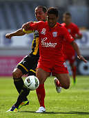 Cassio of Adelaide United is tackled by Lee Bertos of the Wellington Phoenix during the round seven ALeague match between the Wellington Phoenix and...