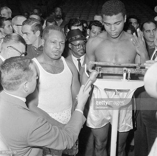 Cassius Clay appears to have his fingers crossed as he tips the scales at 204 lbs during the weighin on the morning of November 15th His rival who...
