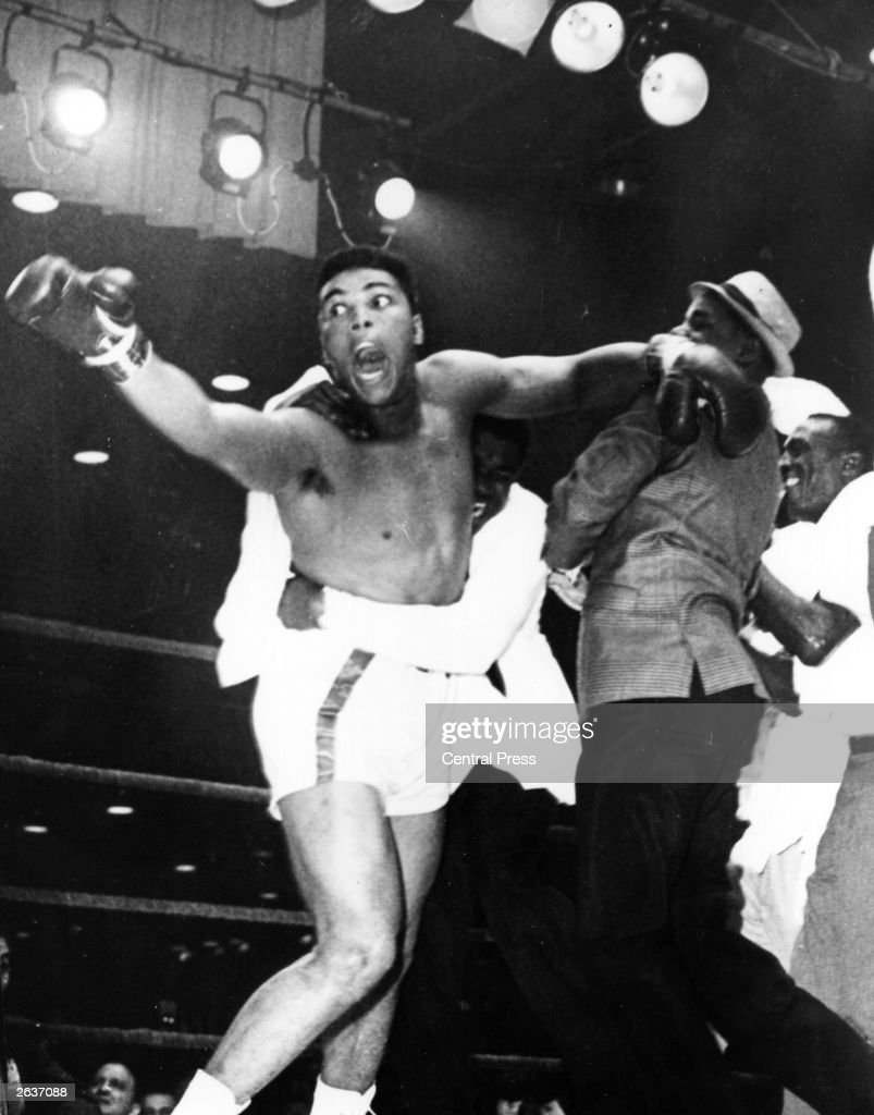 Cassius Clay being restrained by his seconds as he rushes across the ring after his world heavyweight title fight victory over Sonny Liston yelling...